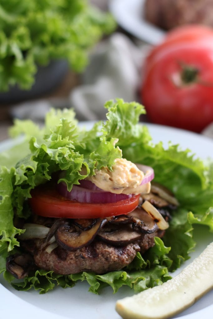 Grilled burger topped with mushrooms, onions, tomatoes onion and mayo wrapped in a lettuce leaf on a plate. Tomato and lettuce in the background