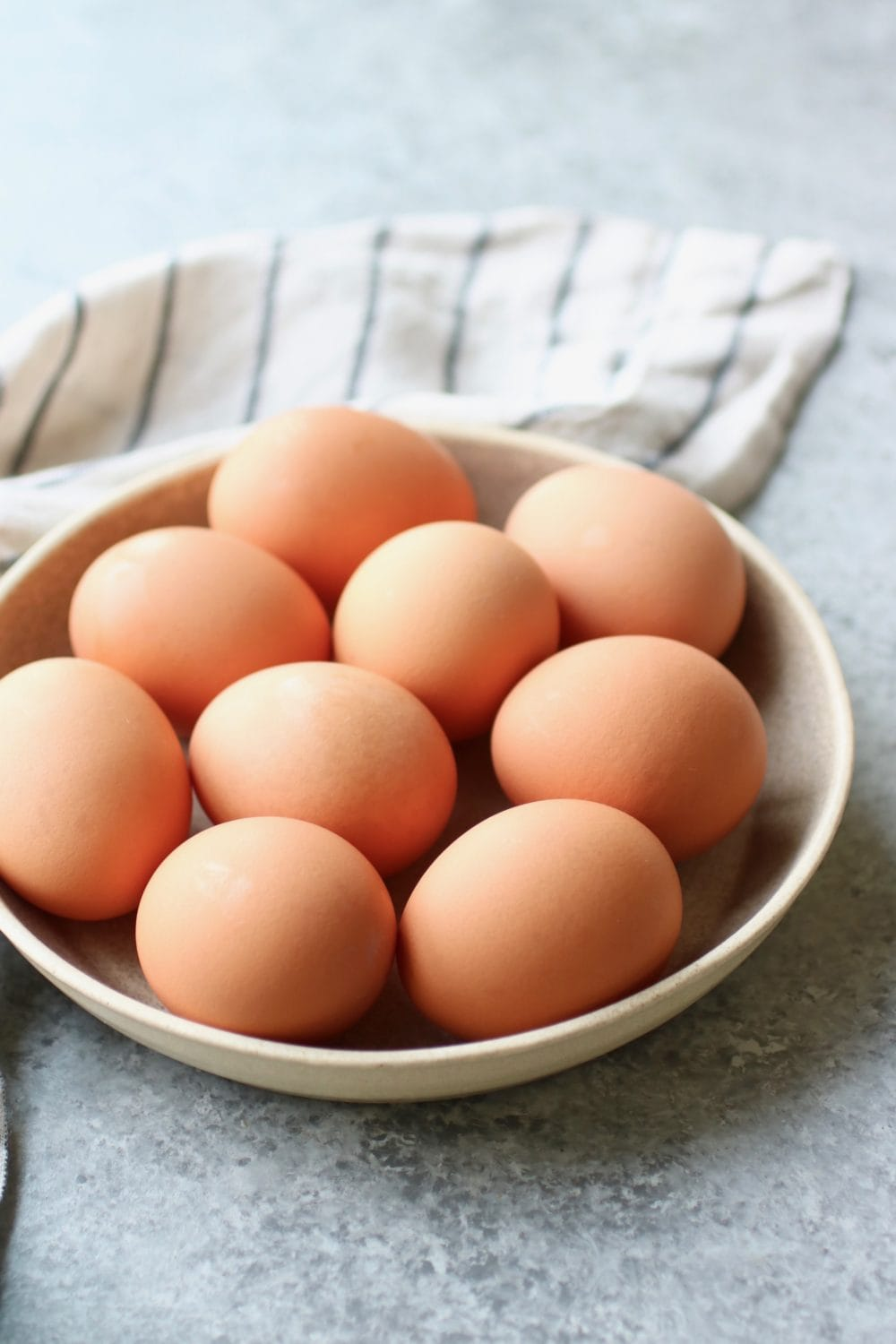 A low profile bowl filled with brown eggs ready to be made into hard-boiled eggs