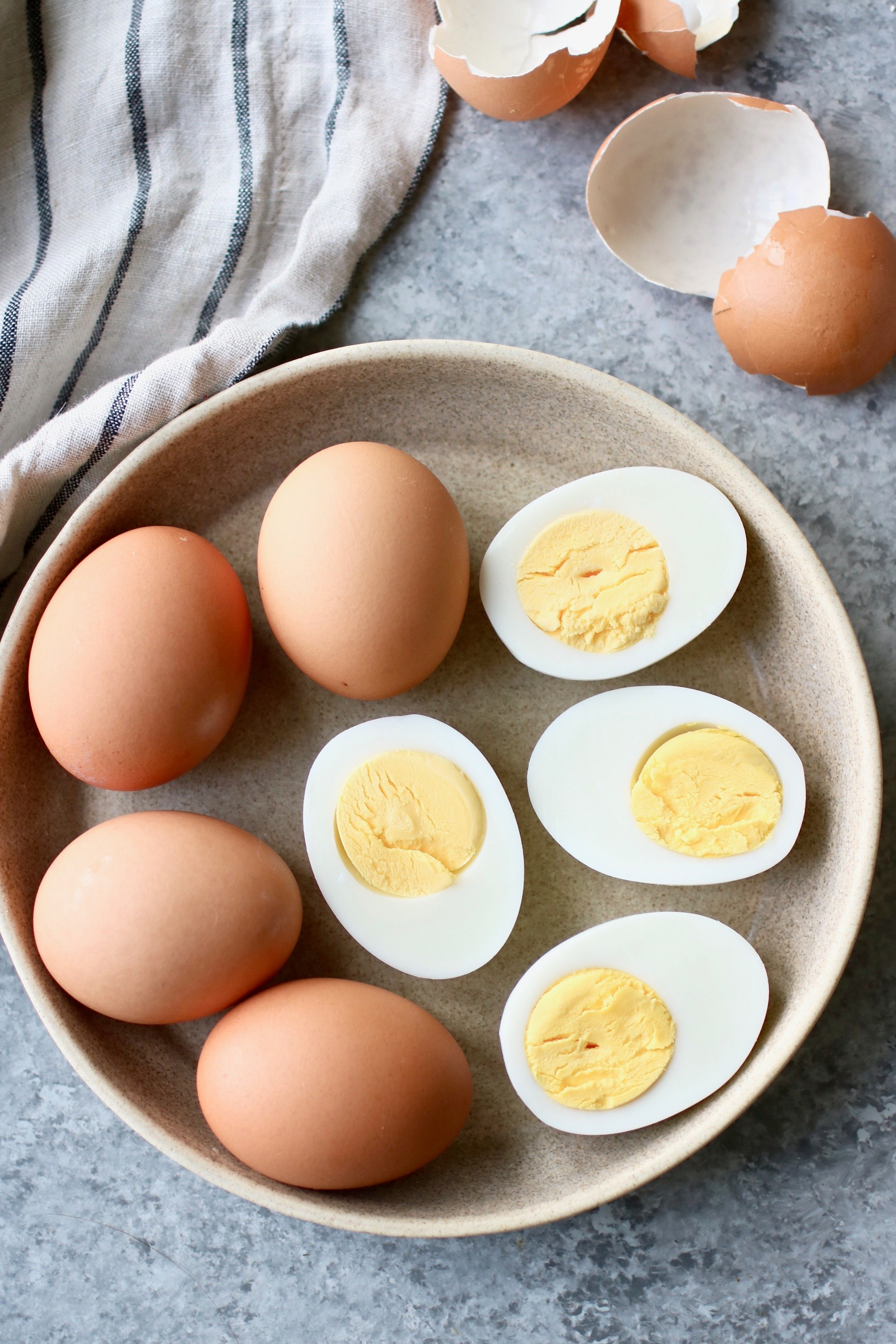 Overhead photo of Easy-Peel Hard Boiled Eggs on a small, cream colored plate. Four of the eggs with shells on next to four hard boiled egg halves showing yolks.