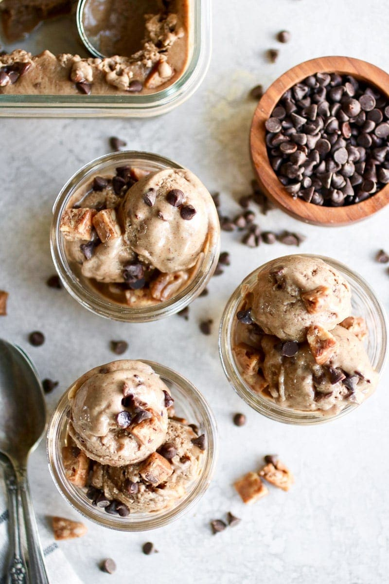 Photo of three servings of Almond Butter Banana Nice Cream served in a small mason jar topped with chocolate chips and pieces of Caveman Collagen Bar.
