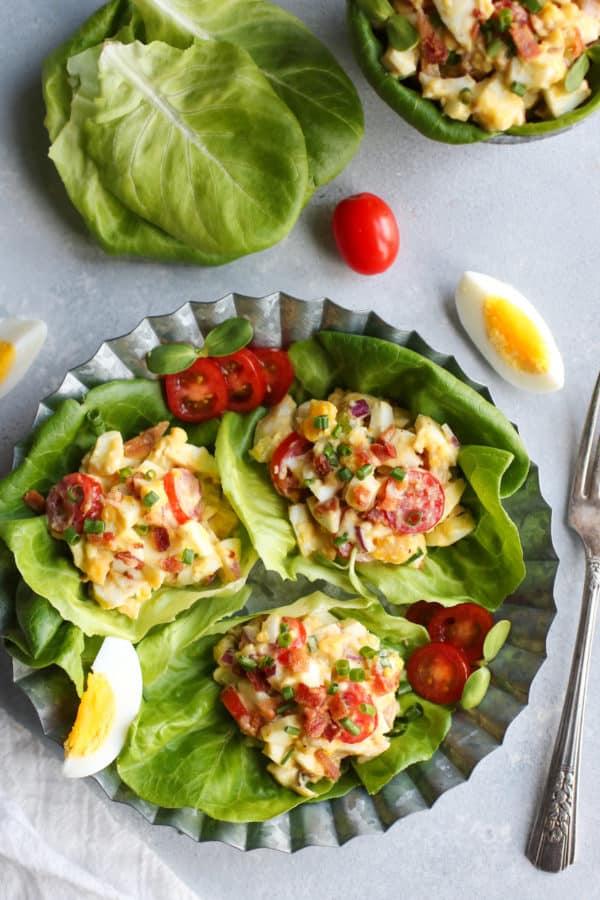 Three BLT egg salad lettuce wraps on a metal tray
