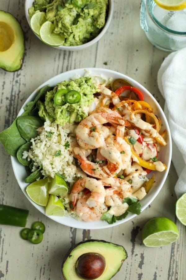 Overhead photo of One-Pan Shrimp Fajita Bowls with limes and avocado halves next to it. Photo is linked to the recipe.