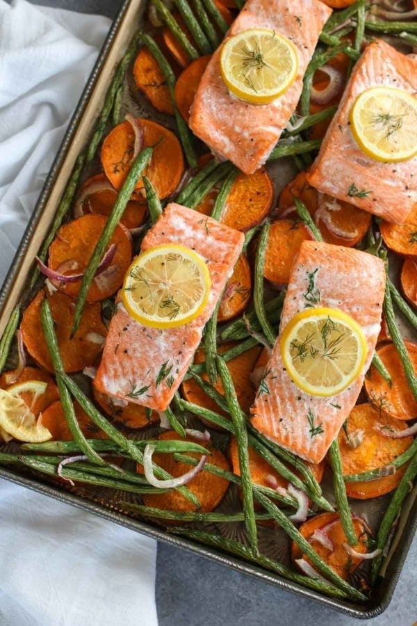 Overhead photo of One-Pan Salmon and Veggie Bake (salmon filets over a bed of sliced sweet potatoes, red onion and green beans. Photo is linked to the recipe.
