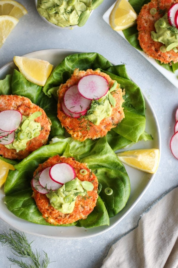 Overhead view of Salmon Burgers with Avocado-Garlic Sauce on a plate. Photo is linked to the recipe.