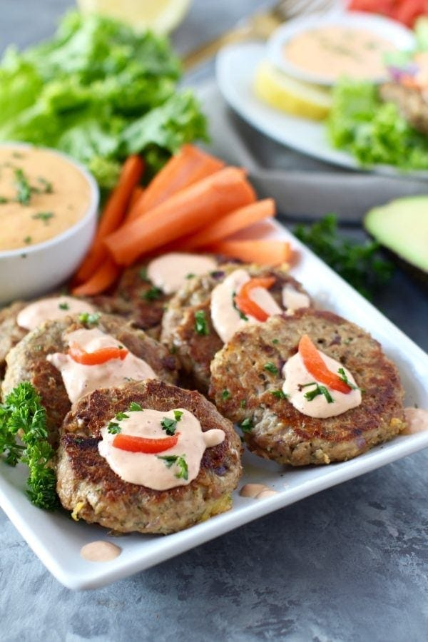 Photo of Easy Tuna Cakes with Red Pepper Mayo on a tray with carrot sticks. Photo is linked to the recipe.