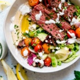 Birdseye view of Mediterranean Steak Bowls with hummus and drizzled with herb-yogurt dressing.