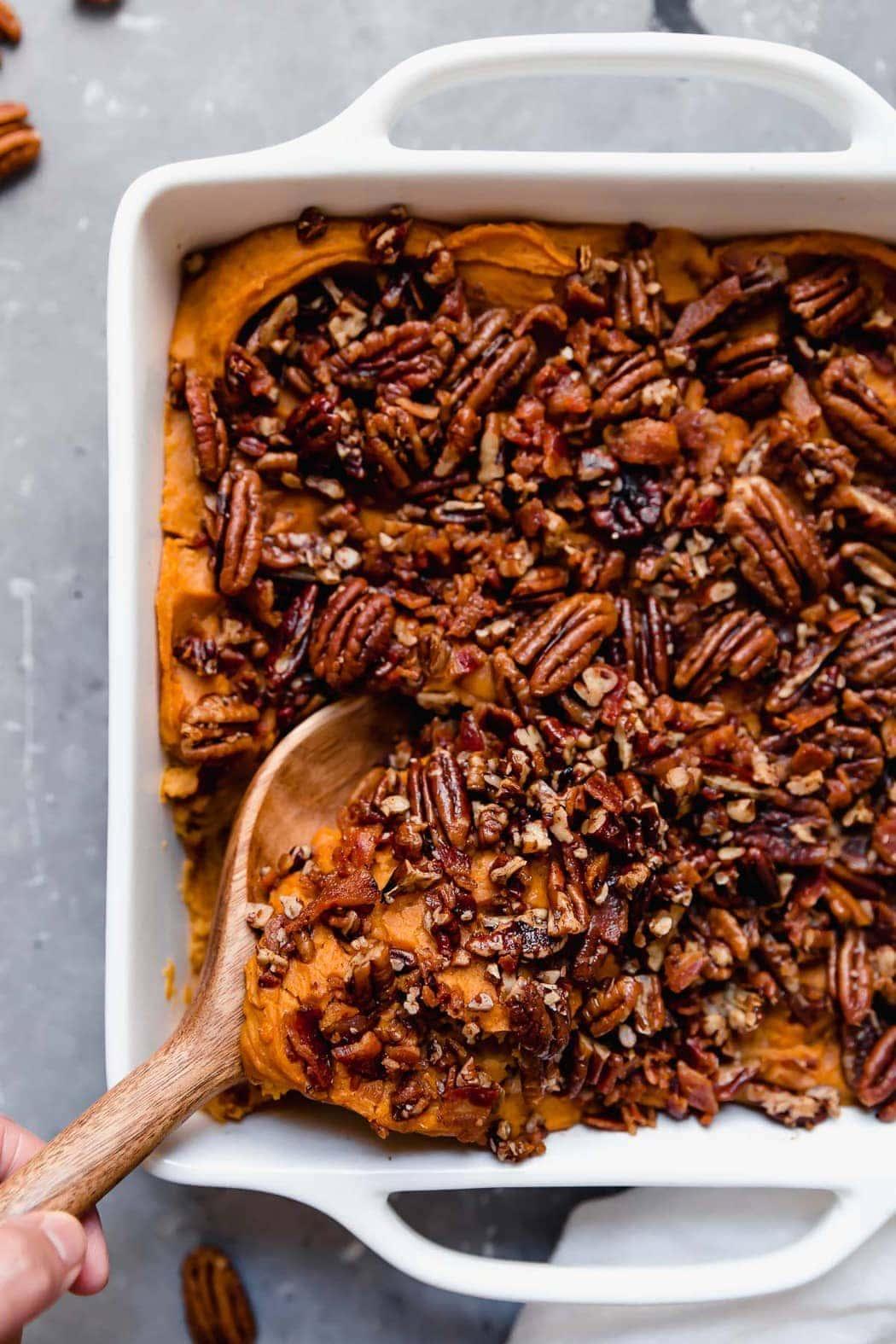 Healthy Sweet Potato Casserole in square white baking dish covered in pecans with a scoop being taken out with a wooden spoon. Part of the 12 Healthy Thanksgiving Side Dish Recipes.