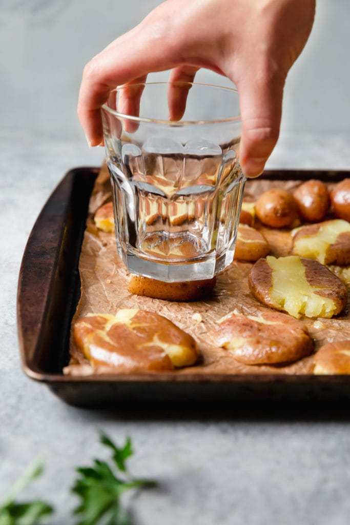 Soft potatoes being 'smashed' by a drinking glass on a baking sheet