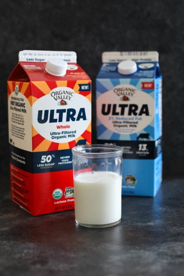 Glass of milk with two cartons of milk in the background.