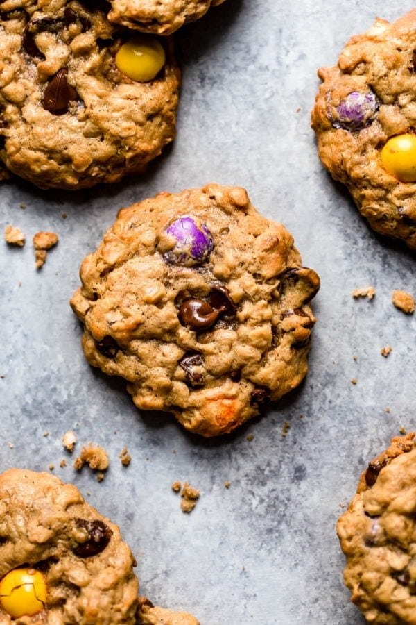 Monster cookies with multi-colored candy chocolate pieces scattered on gray surface