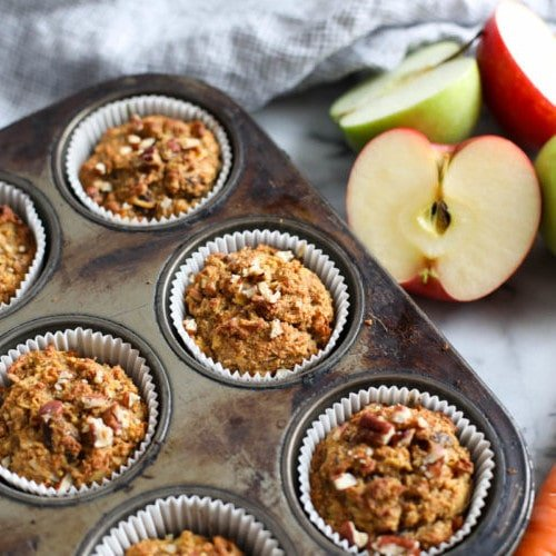 A pan of Paleo Morning Glory Muffins with apples and carrots next to it.