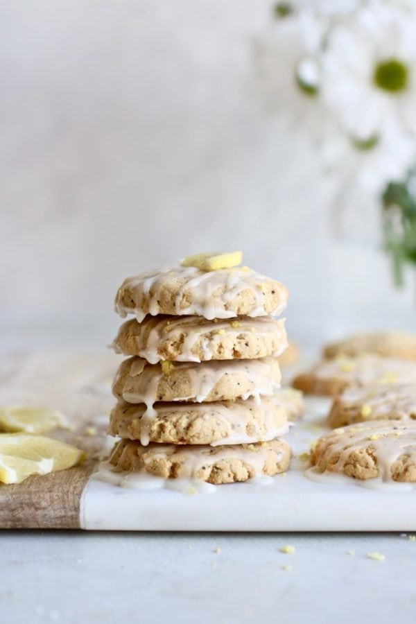 Stack of lemon poppyseed cookies on wooden cutting board, surrounded by lemon garnish and white flowers in the background