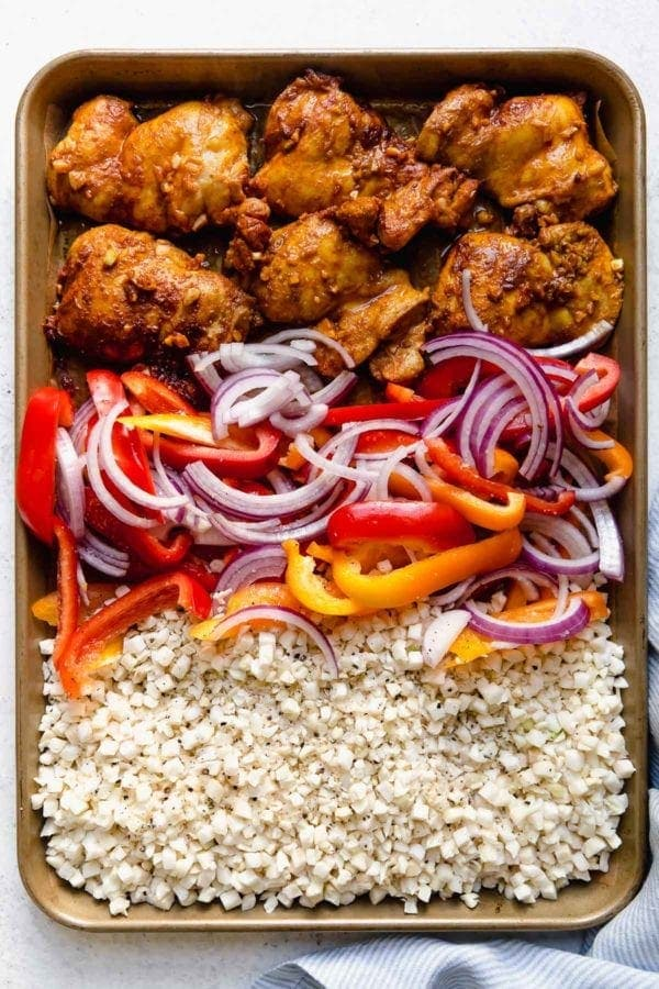 A sheet pan filled with marinated chicken thighs, bell peppers, red onions, and rice cauliflower used to create Sheet Pan Chicken Shawarma Bowls.