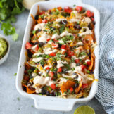 White ceramic casserole dish filled with sweet potato chips topped with melted cheese, shredded chicken, black beans, salsa, diced tomatoes, and a Southwest Ranch Dressing to create the ultimate Loaded Sweet Potato Nachos.