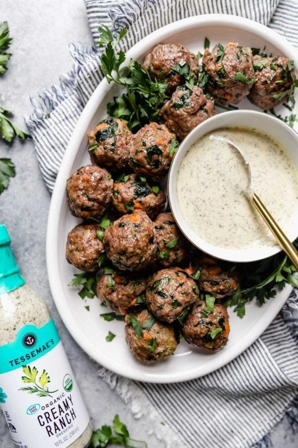 Overhead view of a white platter of the ultimate meal prep meatballs served with a small bowl of ranch dressing on the platter and a bottle of Tessemae's Organic Creamy Ranch Dressing to the side of the platter.