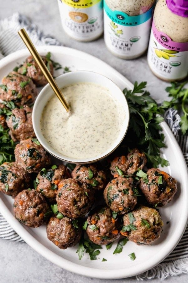 A white platter of the ultimate meal prep meatballs served with a small bowl of ranch dressing with a trio of Tessemae's dressings next to the platter.