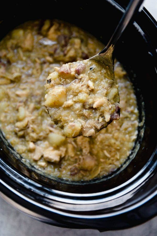 A spoon scoops a portion of Slow Cooker Chicken Chile Verde Stew out of a black slow cooker.