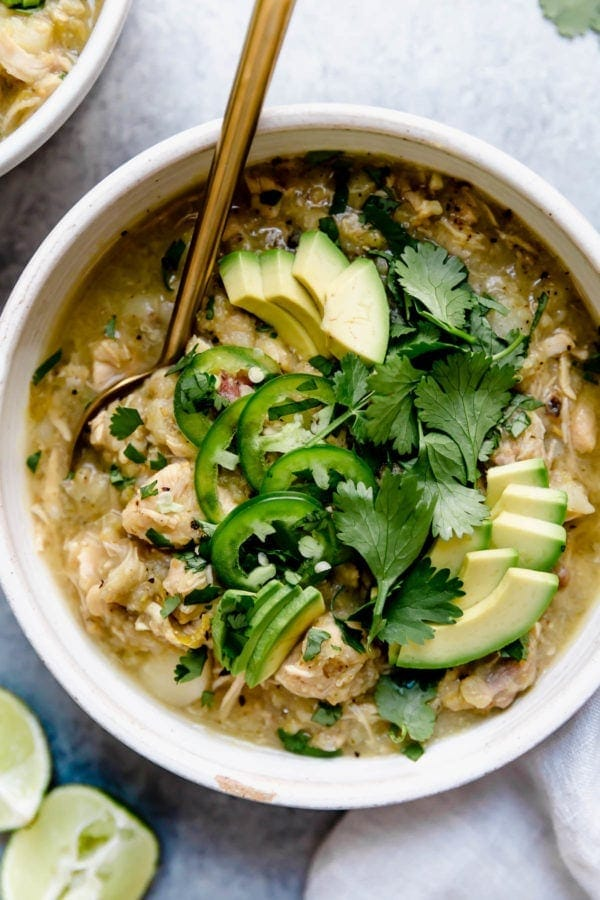 A white bowl filled with Slow Cooker Chicken Chile Verde Stew and topped with fresh cilantro, jalapeño slices, and avocado.