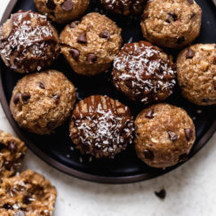 A plate filled with Almond Joy Protein Bites with one bite cut in half to show texture.