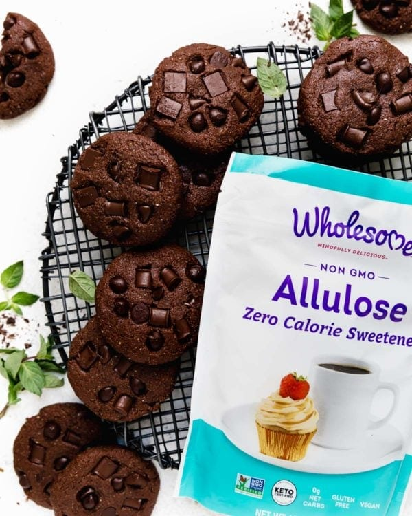 A pile of Low Sugar Double Chocolate Mint Cookies on a round, black cooling rack next to a bag of Wholesome Allulose Zero-Calorie Granulated Sweetener.