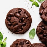 Low Sugar Double Chocolate Mint Cookies studded with chocolate chips and chunks on a white surface surrounded by fresh mint leaves.