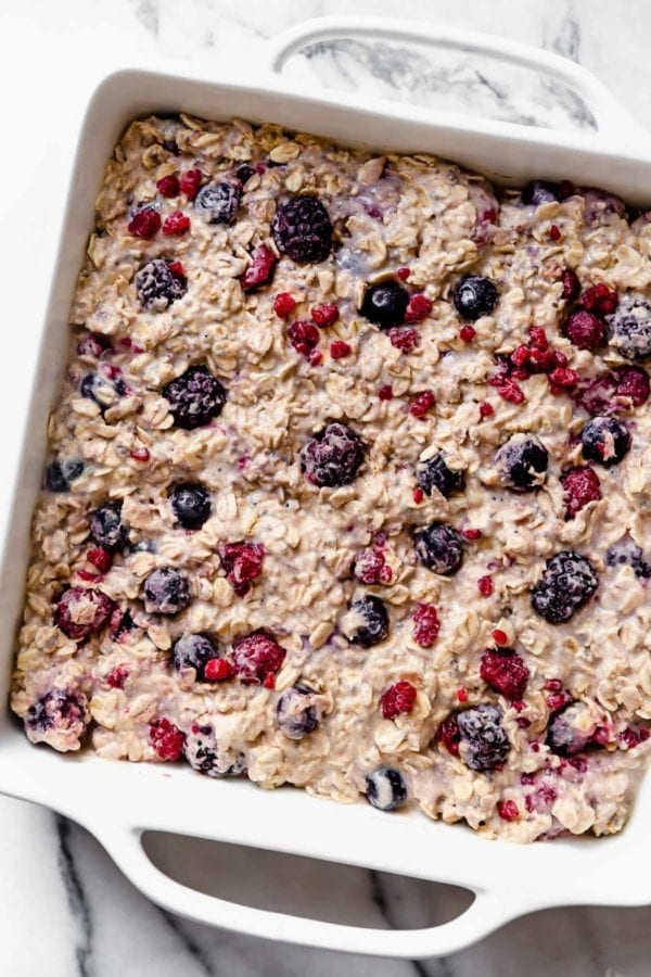 A white square dish is filled with a berry-studded oat mixture to make our Mixed Berry Baked Oatmeal.