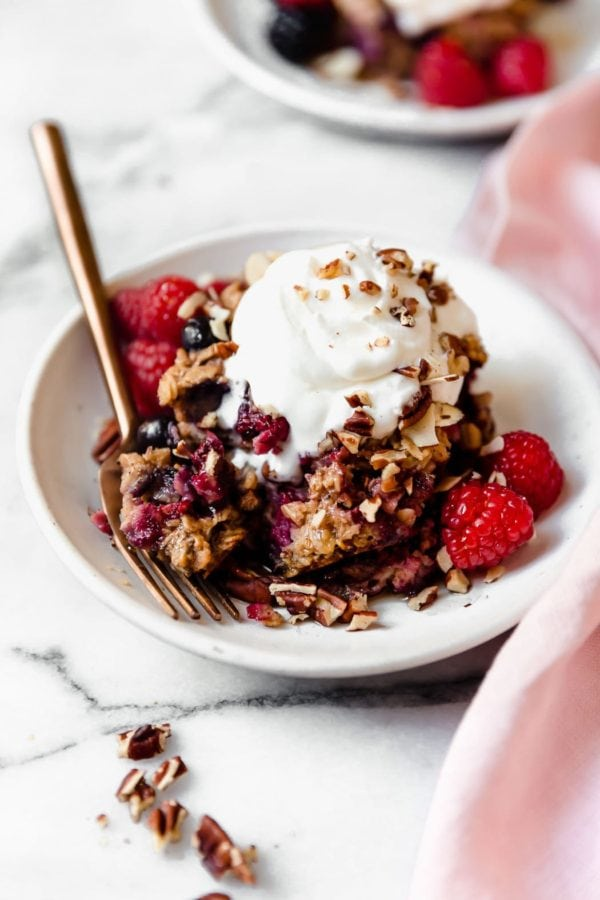 A small white plate holds a serving of Mixed Berry Baked Oatmeal topped with whipped cream and sprinkled with nuts.
