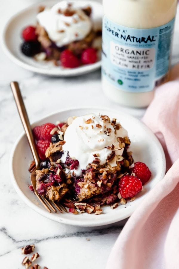 A small white dish holds a serving of Mixed Berry Baked Oatmeal that's topped with whipped cream and sprinkled with toasted nuts ready to be served with a gold fork. In the background, a bottle of Kalona Supernatural Organic Plain Kefir is positioned next to another serving of Mixed Berry Baked Oatmeal.