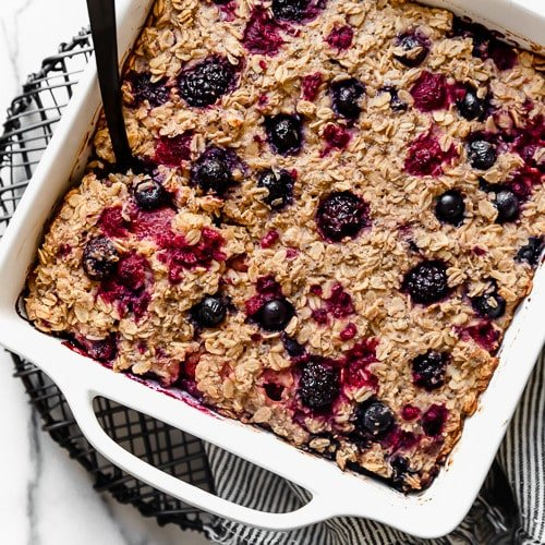 A square white baking dish on a wire cooling rack holds Mixed Berry Baked Oatmeal that's still warm from the oven.