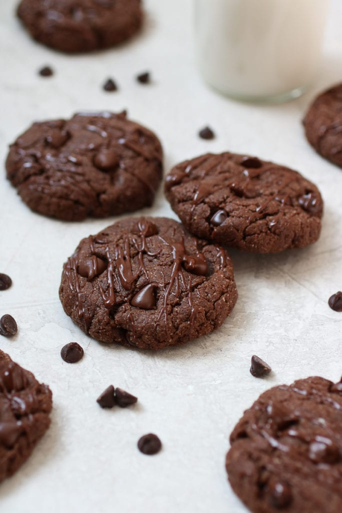 Photo of Chocolate Peanut Butter Protein Cookies on a white table with chocolate chips scattered about.
