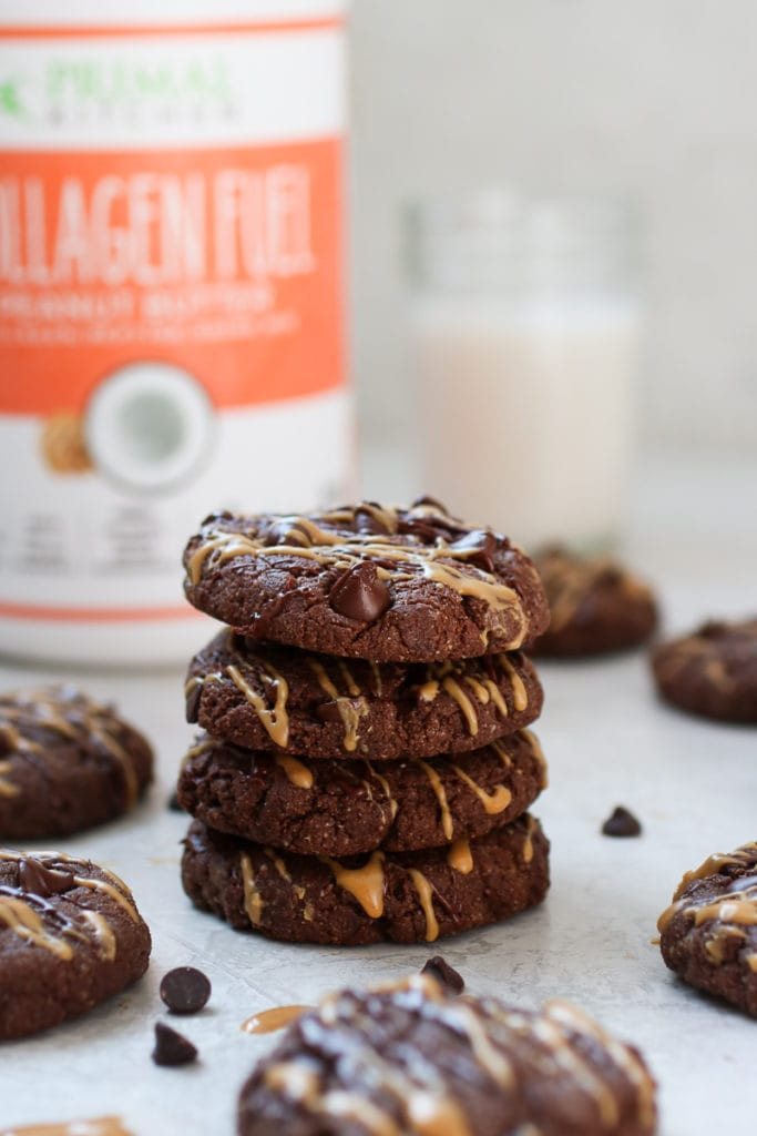 Photo of a stack of Chocolate Peanut Butter Protein Cookies with canister of Primal Kitchen Collagen Fuel in the background. Cookies are drizzled with melted chocolate and peanut butter.
