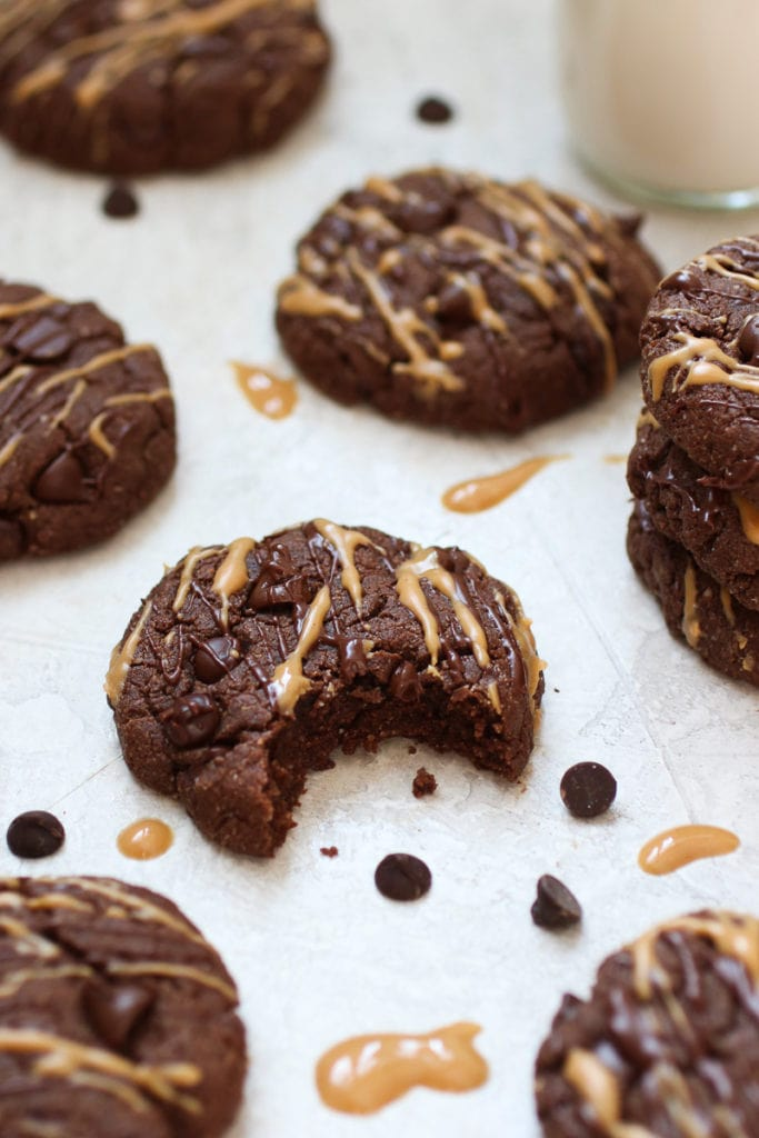 Photo of Chocolate Peanut Butter Protein Cookies drizzled with chocolate and peanut butter. Cookie in the center of the photos has a bite out of it.