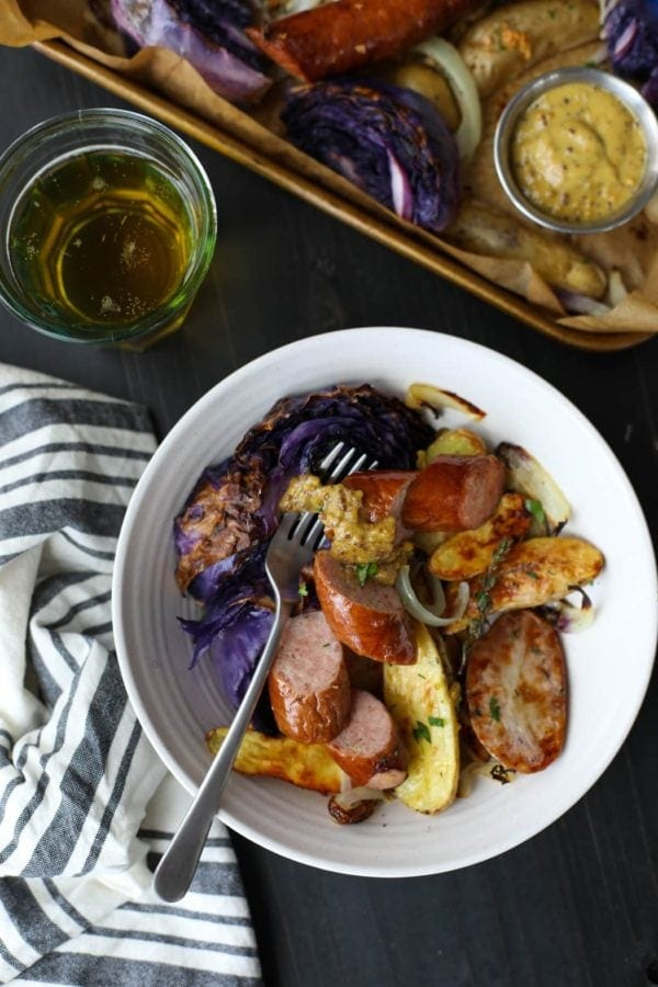 Overhead view of a portion of Sheet Pan Kielbasa, Cabbage and Potatoes served in a white bowl with a glass of lager.