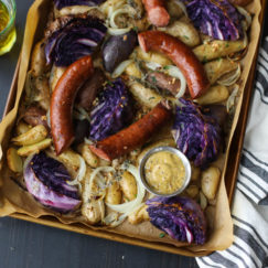 Overhead view of Sheet Pan Kielbasa Cabbage and Potatoes on a dark background with a white towel and a glass of lager off to the side.