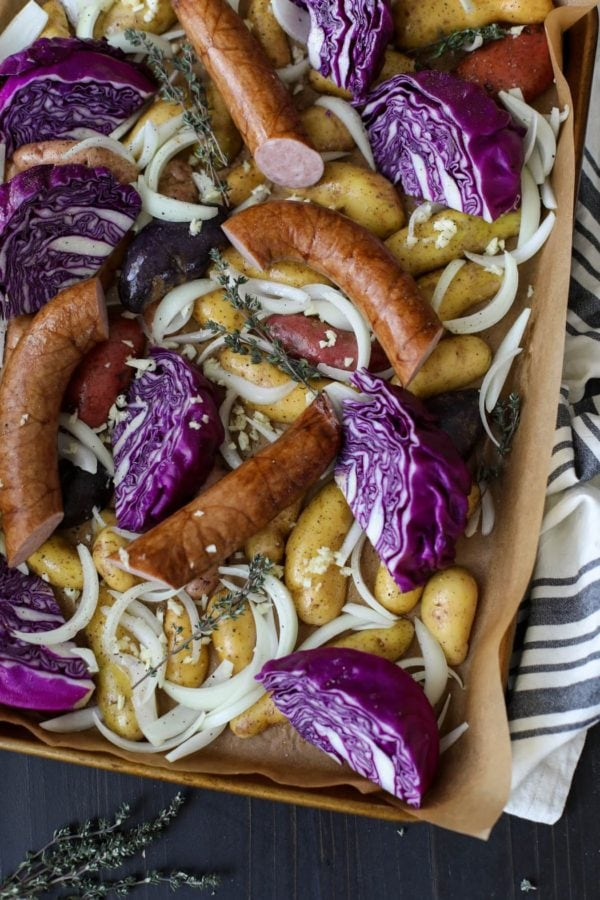 Overhead shot of a potatoes, onions, purple cabbage, and kielbasa on a parchment-lined pan to make Sheet Pan Kielbasa, Cabbage and Potatoes.