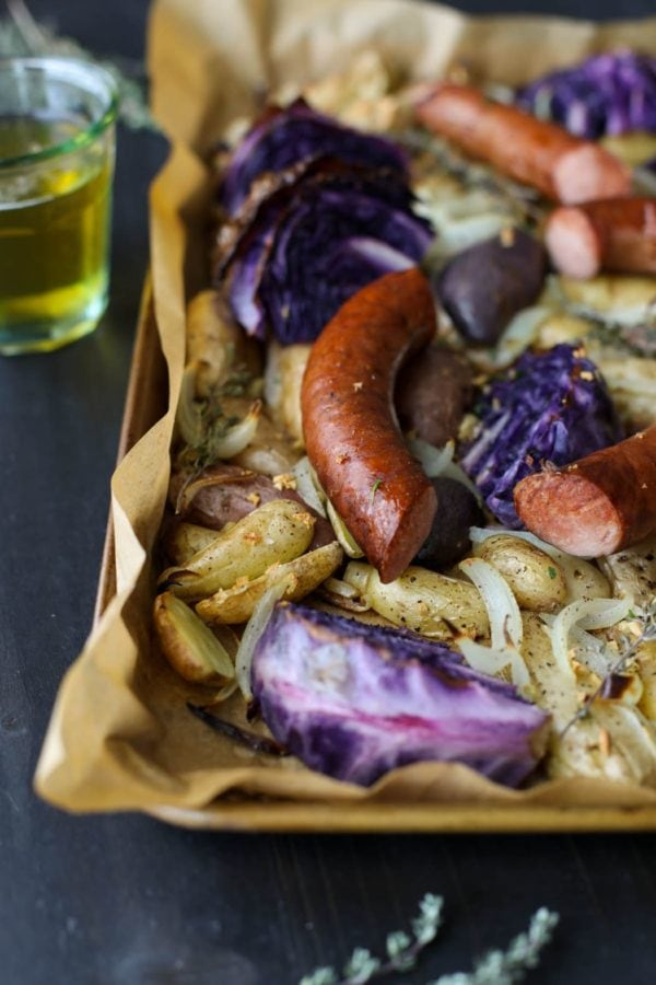 Close up of Sheet Pan Kielbasa, Cabbage and Potatoes with a lager in the background.