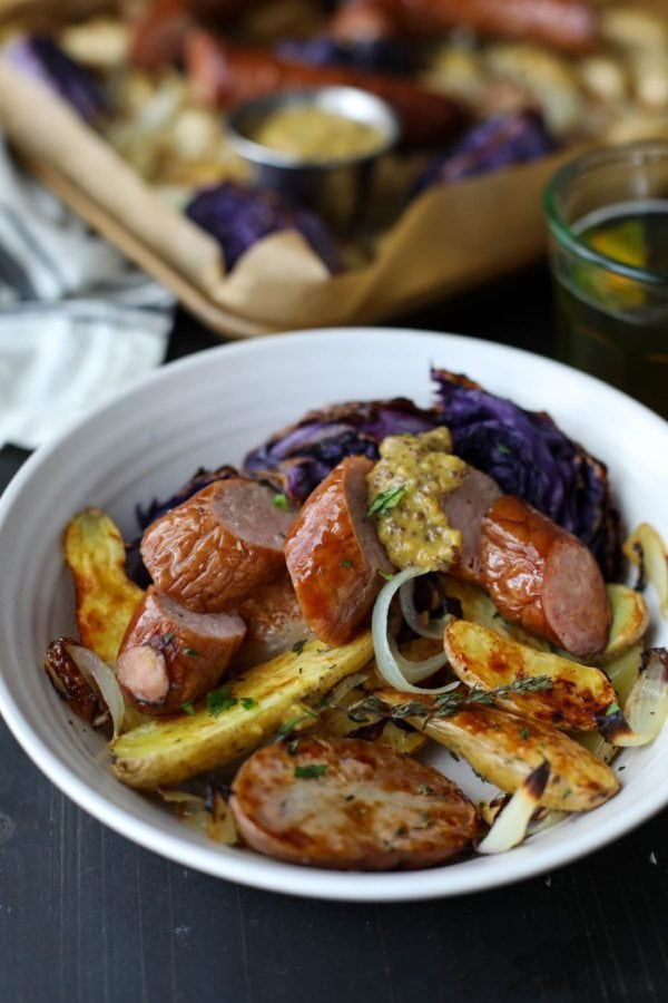 A white bowl piled with roasted potatoes, cabbage, onions, and kielbasa with a generous dollop of grainy mustard.