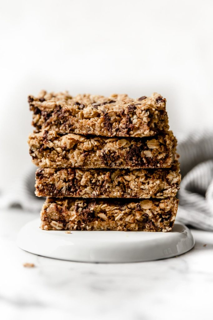 Four soft-baked granola bars stacked vertically on top of a white plate