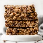 Four peanut butter baked granola bars with chocolate chips stacked on top of each other on a white plate
