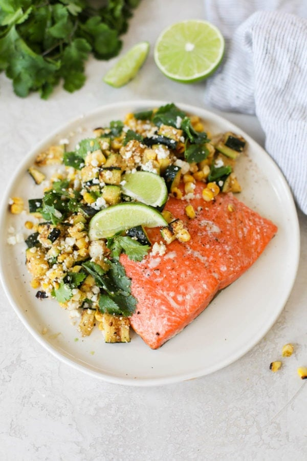 A white plate of Grilled Salmon with Elote Style Veggies sitting next to a light grey striped napkin