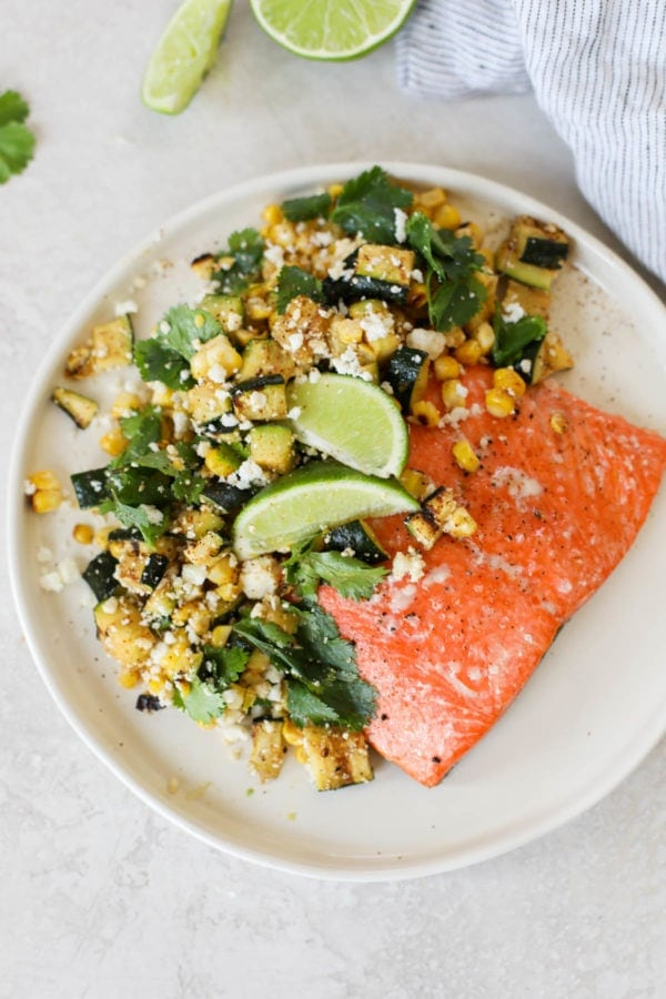 Overhead view of Grilled Salmon with Elote Style Veggies featuring a bright red piece of salmon topped with a pile of grilled corn and zucchini tossed with fresh lime juice and cotija cheese.