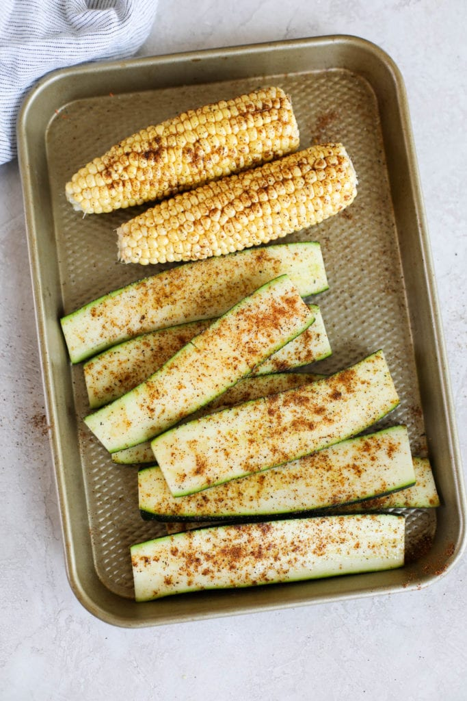 A sheet pan with sliced zucchini and corn on the cob that have been seasoned with chili powder and cumin before grilling.
