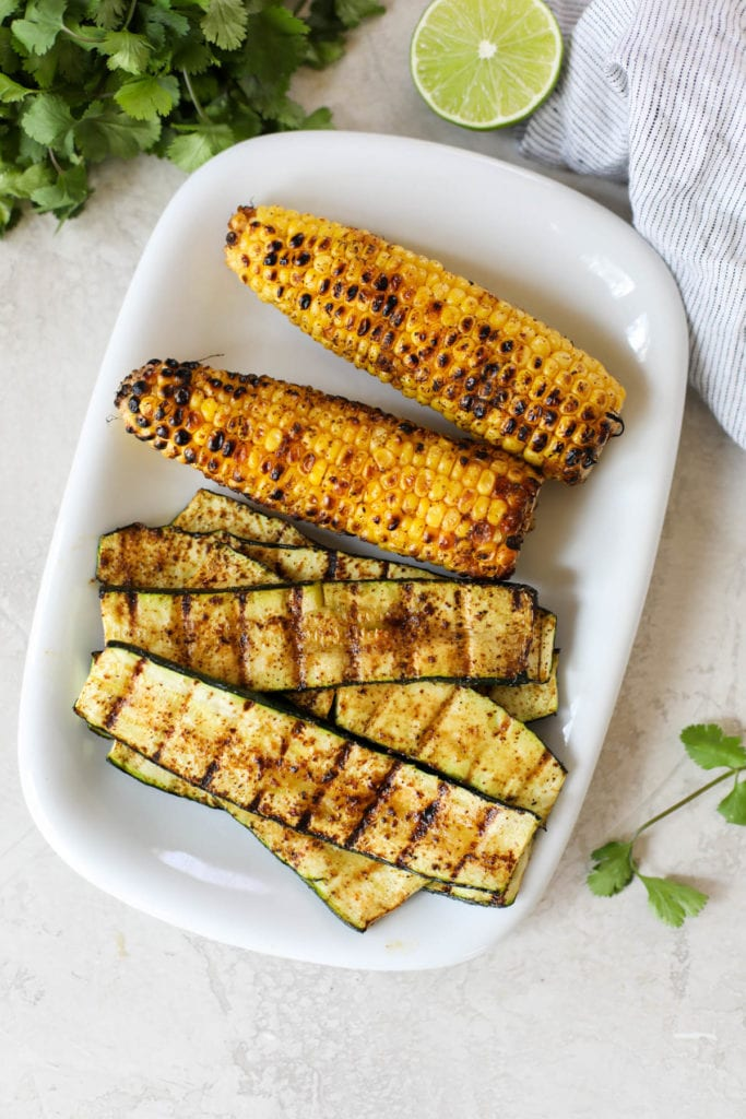 A rectangular white platter with grilled zucchini and corn - both are nicely grilled marked and slightly charred to make Grilled Salmon with Elote Style Veggies