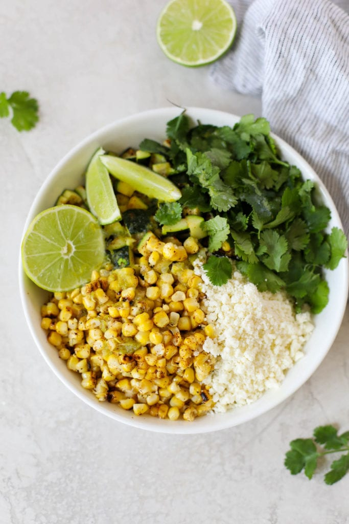 A white bowl with grilled corn (cut from the cob), diced grilled zucchini, cilantro, lime juice, and crumbed cotija cheese.