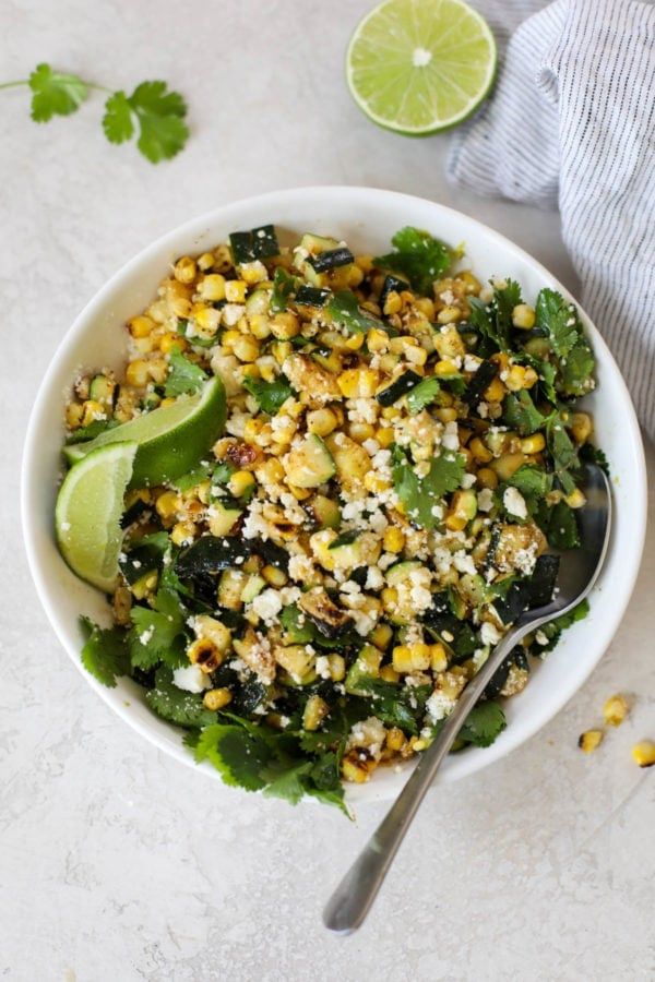 A white bowl of grilled corn and zucchini tossed with cilantro, lime juice, and cotija cheese.