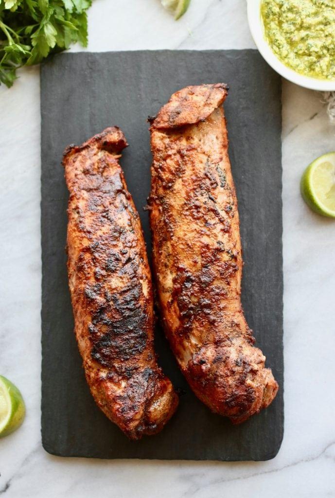 Black serving board holding two Grilled Pork Tenderloins
