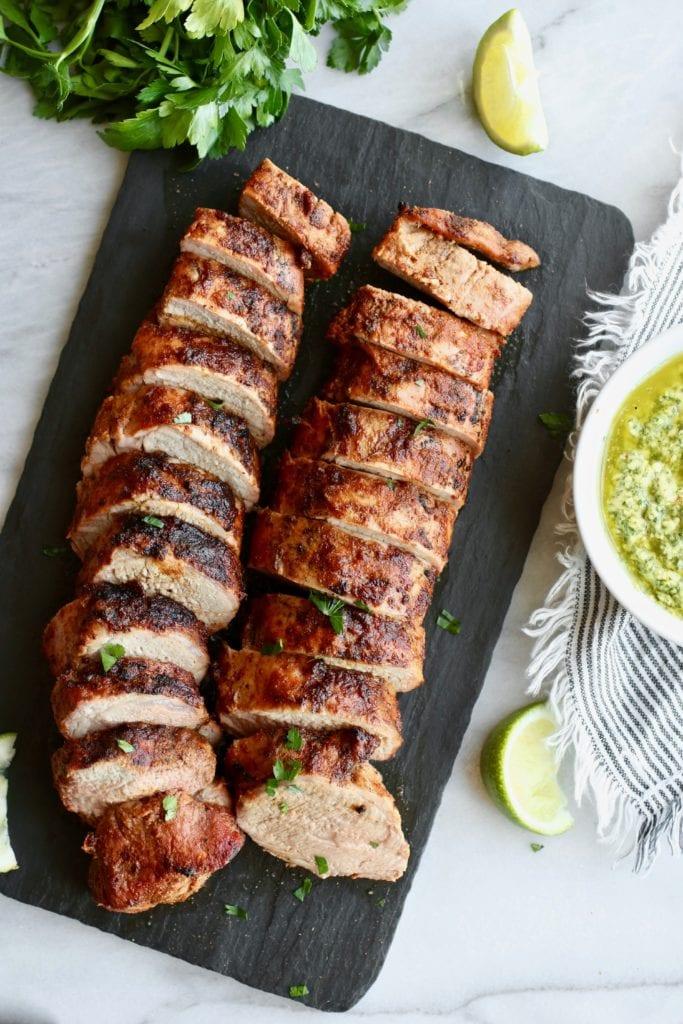 Black serving board holding two sliced Grilled Pork Tenderloins