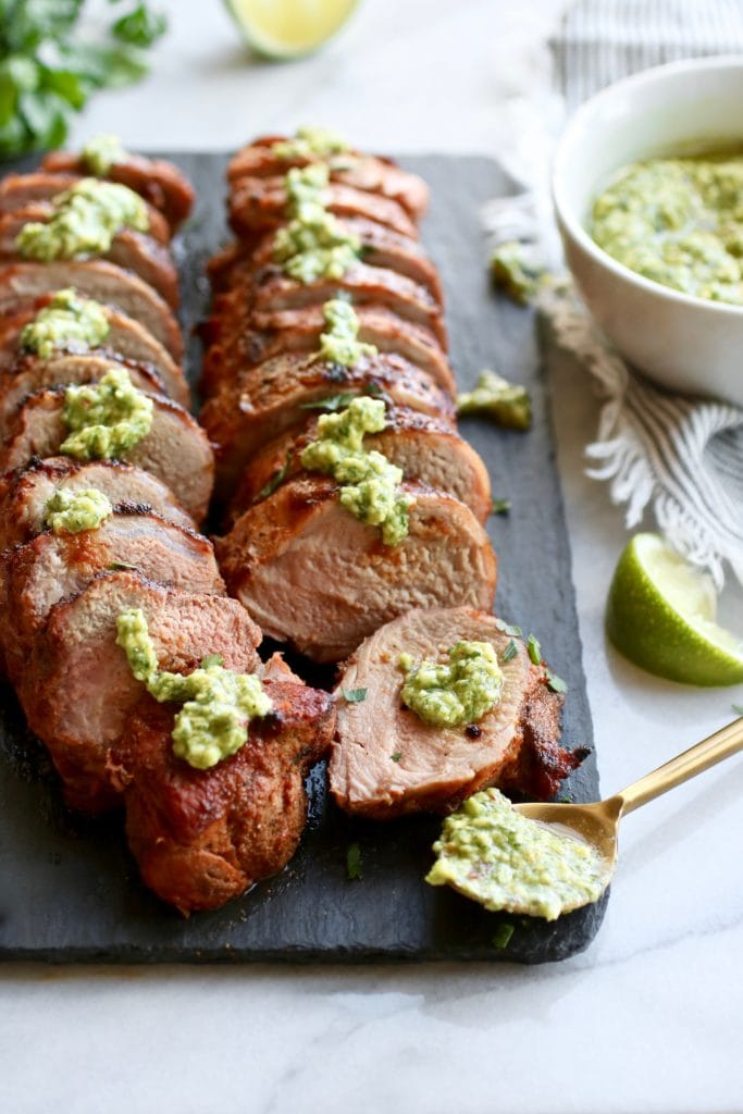 Photo of Grilled Pork Tenderloin on a black serving board topped with Avocado Green Sauce.