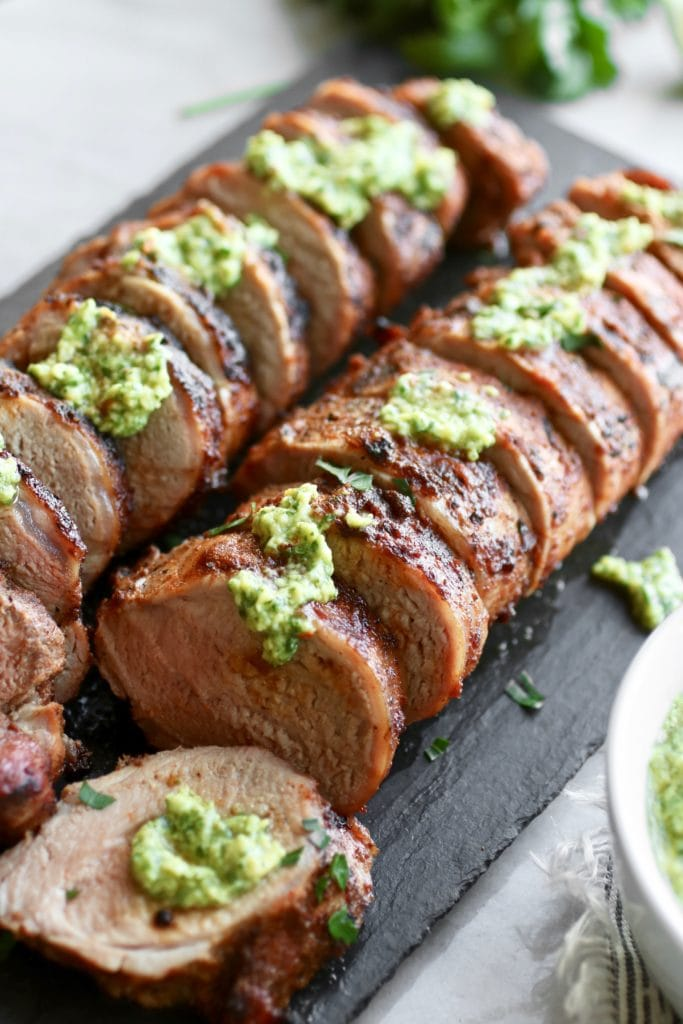 Photo of Grilled Pork Tenderloin flavored with the Ultimate BBQ Rub and topped with Avocado Green Sauce.