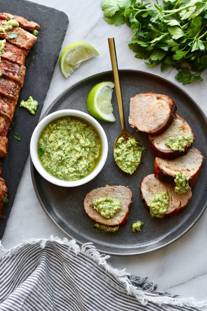 Photo of Grilled Pork Tenderloin sliced, topped with avocado green sauce and served on a plate with a white bowl holding avocado green sauce.